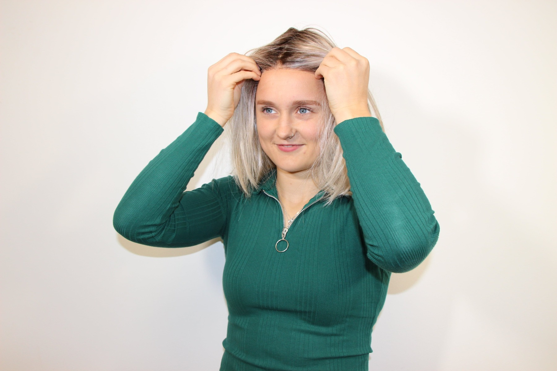 Lady aligning the wig ear points to position the wig securely on her head