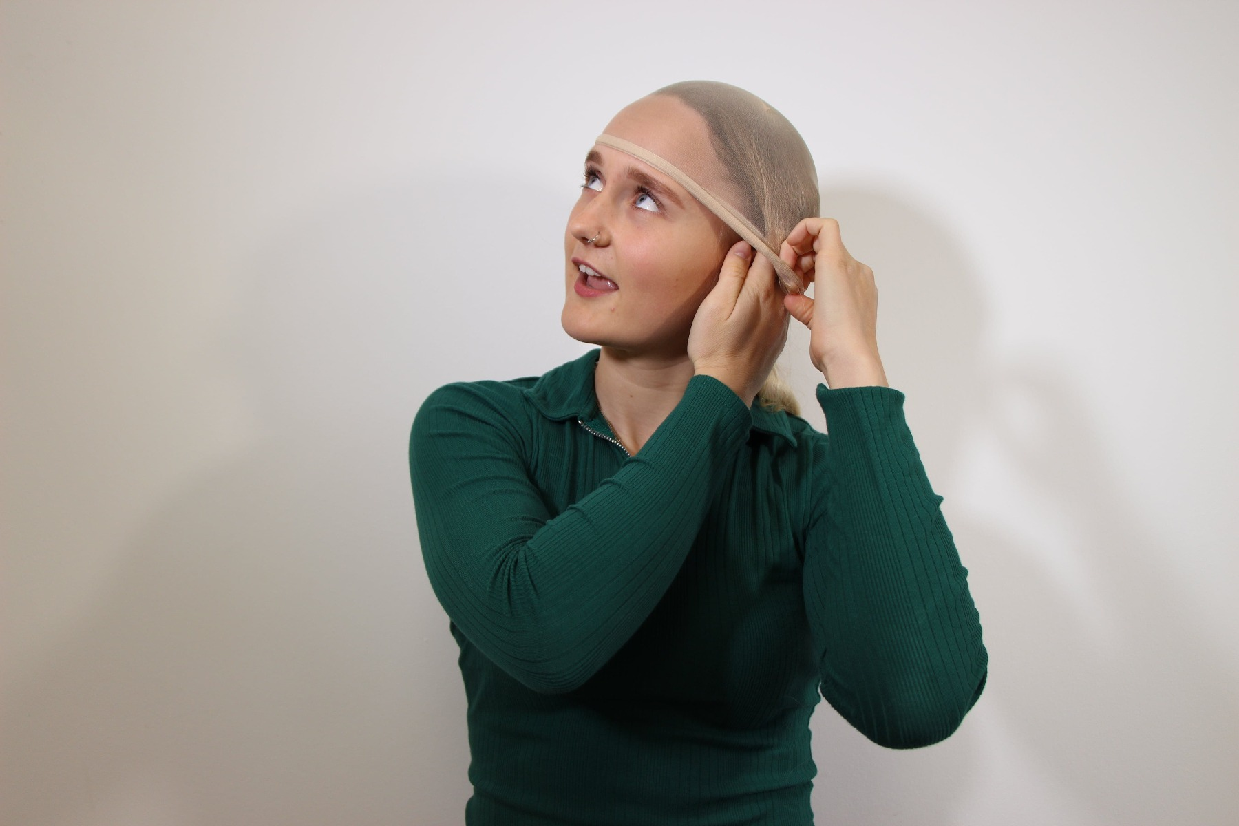 Lady tucking excess hair into her wig cap