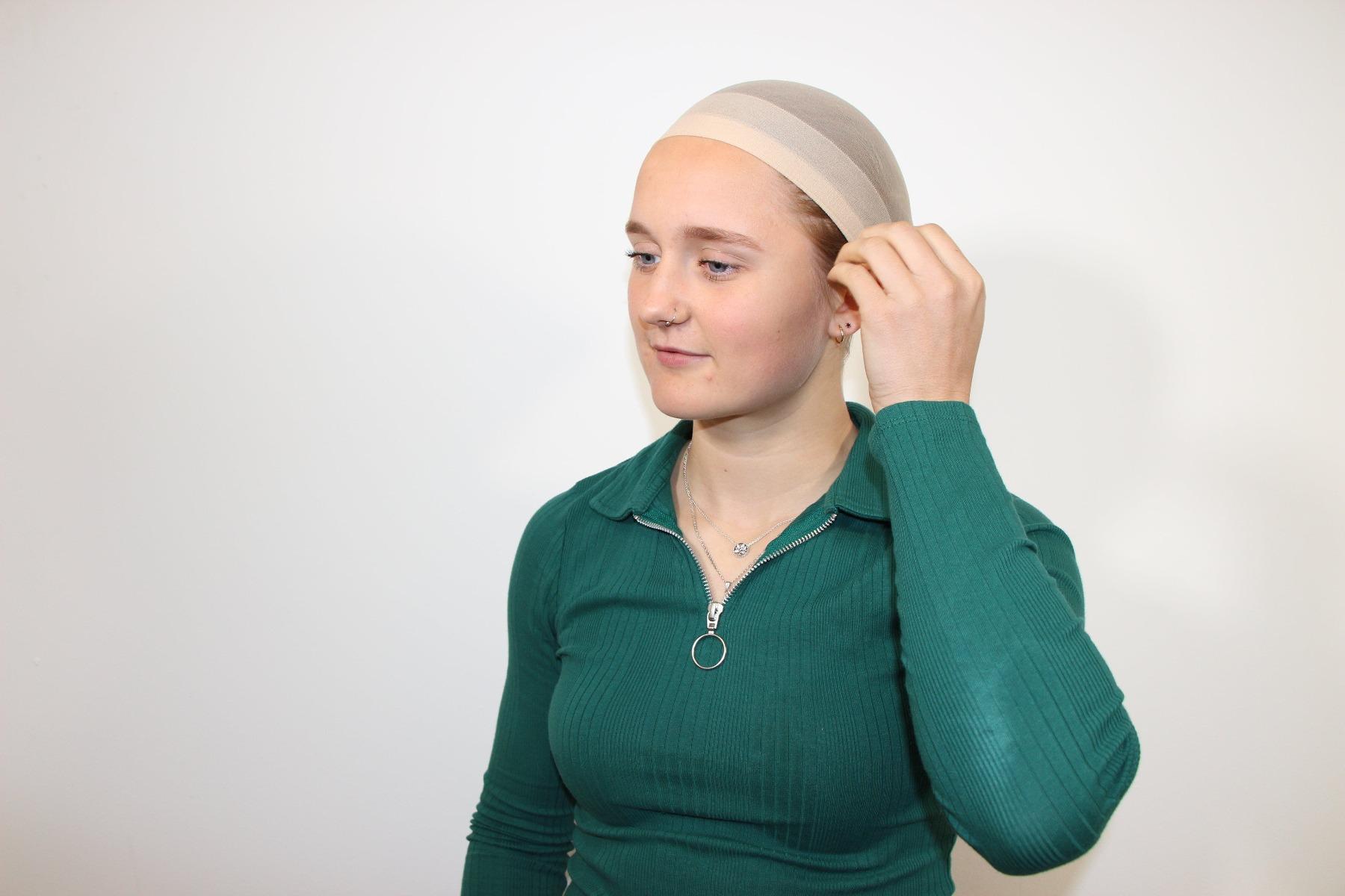 Lady tucking wig cap behind her ears