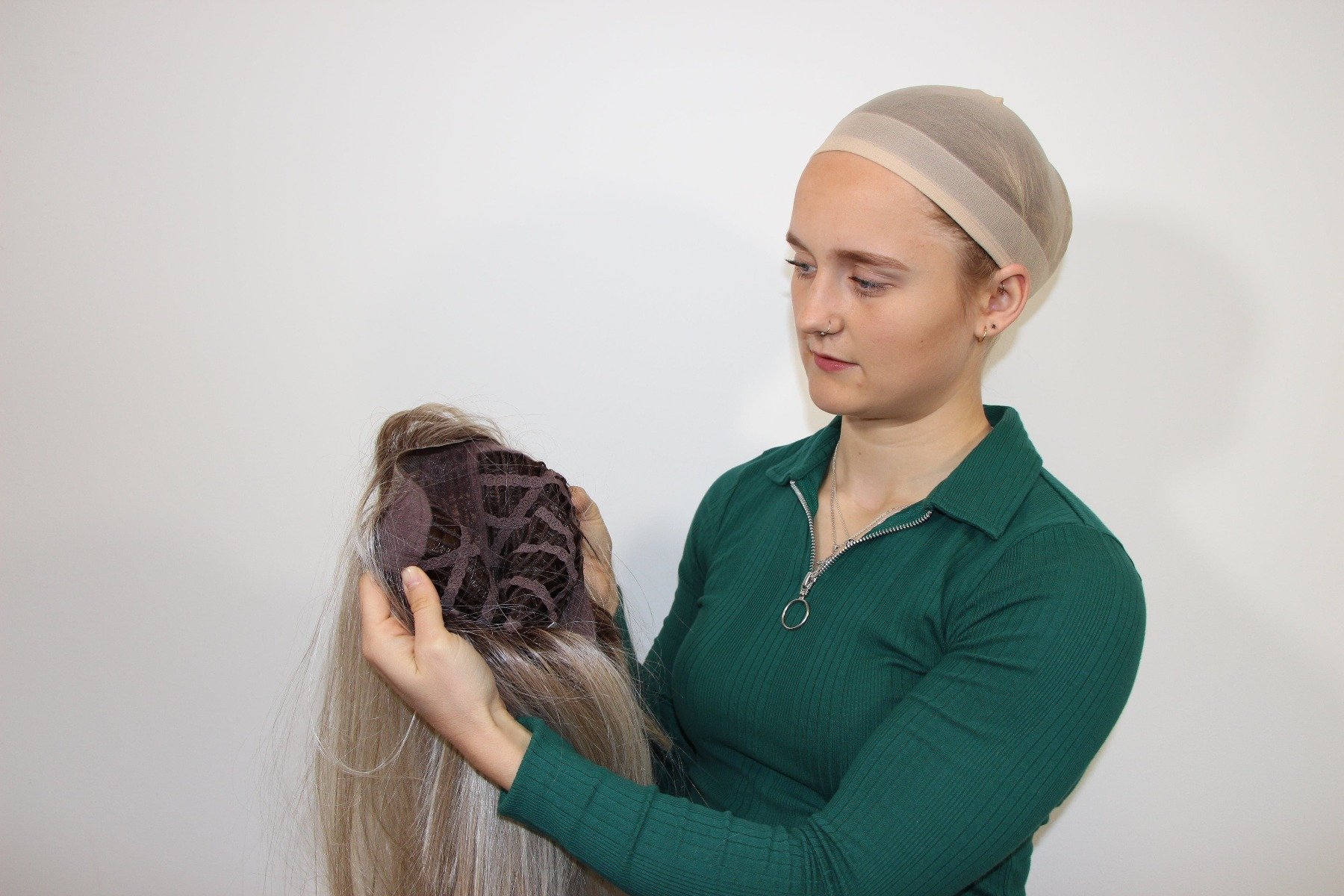 Lady finding the ear points on her wig